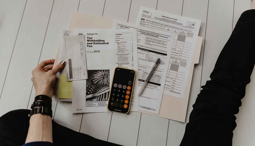 Tax papers on a table with calculator and pen