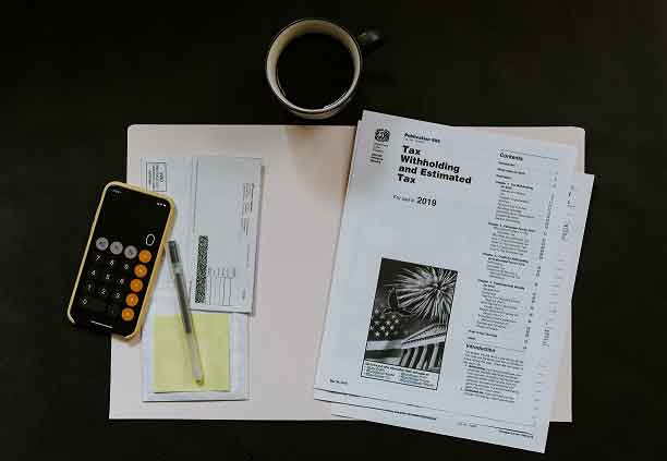 coffee, tax papers and calculator on black background