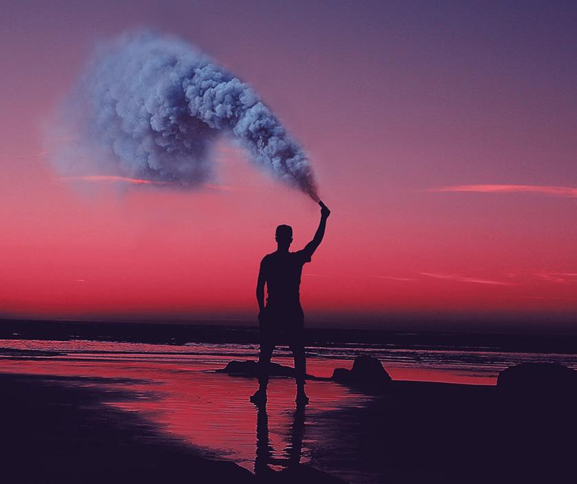 man holding smoke firework at sunset
